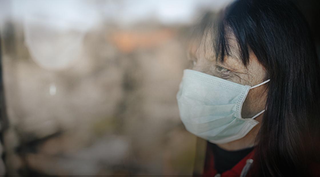 Senior woman wearing a mask looking through nursing home window