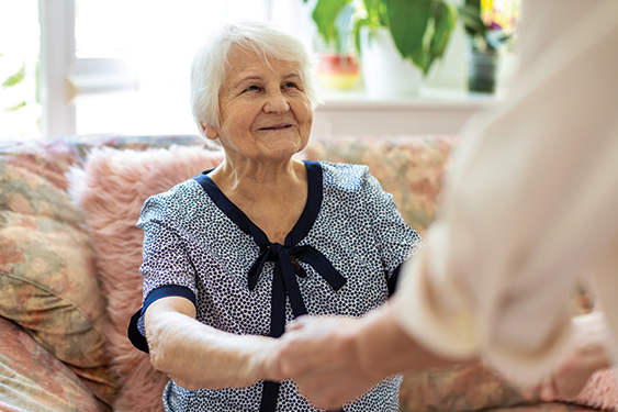 Female caretaker supporting old woman to stand up from the sofa
